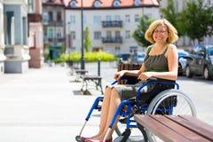 Jonge volwassen vrouw op rolstoel op de straat Stock Fotografie