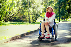 Jonge volwassen vrouw op rolstoel in het park Royalty-vrije Stock Fotografie