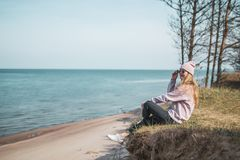 Jonge volwassen vrouw in roze hoedenzitting alleen op bluffs, het kijken van overzees, vrijheidsconcept, vreedzame atmosfeer royalty-vrije stock foto's