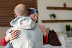 Jonge volwassen vrouwelijke kankerpatiënt die haar echtgenoot thuis na behandeling in het ziekenhuis koesteren Kanker en families royalty-vrije stock fotografie