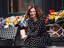 Jonge volwassen vrouwenzitting op de bank het lachen het drinken koffie in openlucht in stadspark Royalty-vrije Stock Afbeelding