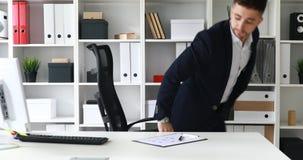 Jonge volwassen zakenman die in werkplaats in modern bureau komen stock video