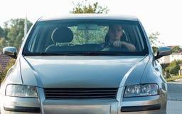 Jonge volwassen zitting in zijn auto en het kijken aan camera door wi Stock Foto