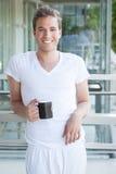Jonge volwassene die een kop van koffie houden Stock Afbeelding