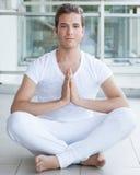 Jonge volwassene die met handen samen mediteren Stock Fotografie