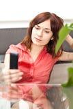 Jonge volwassene met celtelefoon dichtbij de lijst royalty-vrije stock foto