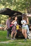Jonge vrienden dichtbij bestelwagen met het kamperen toestel royalty-vrije stock foto's