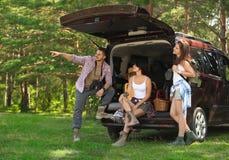 Jonge vrienden dichtbij bestelwagen met het kamperen toestel stock afbeelding