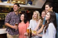 Jonge vrienden die een drank hebben samen Stock Foto's