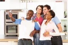 Jonge Vrienden die Foto in Keuken nemen stock afbeeldingen