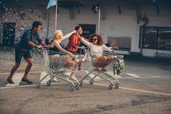 Jonge vrienden die met boodschappenwagentjes rennen Stock Foto