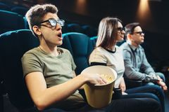 Jonge vrienden die op 3d film in bioskoop letten Stock Afbeeldingen