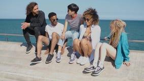In jonge vrienden die op strandboulevard koelen stock video