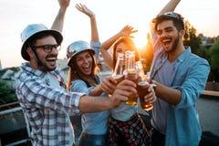 Jonge vrienden die uit met dranken op dak hangen stock afbeeldingen