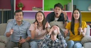 Jonge vrienden die voetbal op spel op TV letten samen thuis en teleurgesteld over hun favoriet team verliezende gelijke stock footage