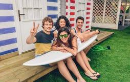 Jonge vrienden die vrouw bovenop surfplank houden Royalty-vrije Stock Afbeelding