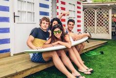 Jonge vrienden die vrouw bovenop surfplank houden Stock Foto