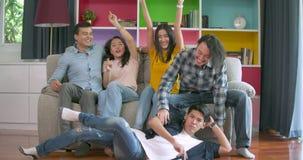 Jonge vrienden en op bank lopen springen die dan en camera glimlachen samen thuis bekijken allen die stock video