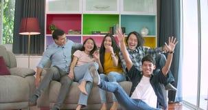 Jonge vrienden en op bank lopen springen die dan en camera glimlachen samen thuis bekijken allen die stock footage