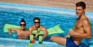 Jonge vrienden in zwembad het glimlachen stock fotografie