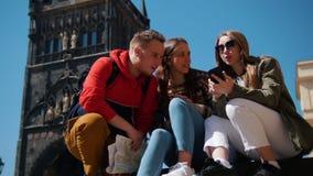 Jonge vriendenreizigers die op een achtergrond van Brugtoren zitten van Charles Bridge en naar een manier zoeken om in hun te gaa stock videobeelden