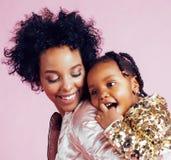 Jonge vrij Afrikaans-Amerikaanse moeder met weinig leuke dochter die, het gelukkige glimlachen op roze achtergrond, levensstijl k royalty-vrije stock foto's