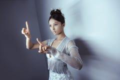 Jonge vrij Aziatische futuristische vrouw die een denkbeeldige knoop, lege ruimte voor knopen drukken Royalty-vrije Stock Foto