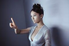 Jonge vrij Aziatische futuristische vrouw die een denkbeeldige knoop, lege ruimte voor knopen drukken Stock Foto's