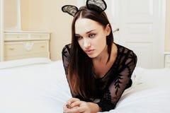 Jonge vrij donkerbruine vrouw die de sexy oren van de kantmuis, dragen die het wachtende dromen in bed leggen Stock Afbeeldingen