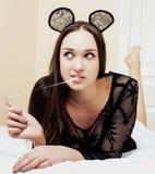 Jonge vrij donkerbruine vrouw die de oren van de kantmuis, dragen die het wachtende dromen in bed leggen Royalty-vrije Stock Foto's