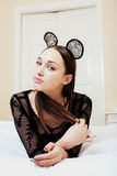 Jonge vrij donkerbruine vrouw die de oren van de kantmuis, dragen die het wachtende dromen in bed leggen Stock Afbeeldingen