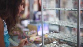 Jonge vrij donkerbruine vrouw die juwelen op showcase bekijken Jonge dame die bijouterie in wandelgalerij genieten van 1920x1080 stock videobeelden