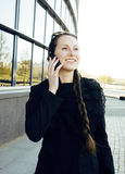 Jonge vrij donkerbruine vrouw die op telefoon spreken die voor de moderne bouw, levensstijl bedrijfsmensenconcept glimlachen Stock Foto