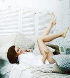 Jonge vrij donkerbruine vrouw in haar slaapkamerzitting bij venster Li stock foto