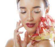 Jonge vrij donkerbruine vrouw met rode dichte die omhooggaand van de bloemamaryllis op witte achtergrond wordt geïsoleerd Buitens royalty-vrije stock afbeelding