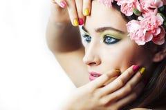 Jonge vrij donkerbruine vrouw met roze bloemen en manicure die vrolijk stellen ge?soleerd op witte close-up als achtergrond royalty-vrije stock foto