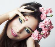 Jonge vrij donkerbruine vrouw met roze bloemen en manicure die vrolijk stellen ge?soleerd op witte close-up als achtergrond royalty-vrije stock afbeeldingen