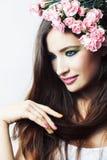 Jonge vrij donkerbruine vrouw met roze bloemen en manicure die vrolijk stellen ge?soleerd op witte close-up als achtergrond stock foto's