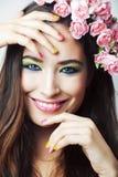 Jonge vrij donkerbruine vrouw met roze bloemen en manicure die vrolijk stellen ge?soleerd op witte close-up als achtergrond royalty-vrije stock fotografie