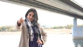 Jonge vrij donkerbruine vrouwenpunten aan camera met vinger - parkeer met brug en rivier op achtergrond stock footage