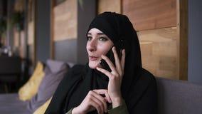 Jonge vrij moslimvrouw met make-up in hijab die op telefoon spreken en glimlachen, die in vrolijke koffie zitten, Zachte nadruk stock videobeelden