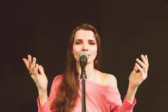 Jonge vrij vrouwelijke prediker die in mic spreken stock foto