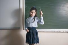 Jonge vrij vrouwelijke privé-leraar gebruikend de studieklasse van het stokonderwijs en zich bevindt op de achtergrond van het kr royalty-vrije stock afbeeldingen