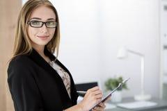 Jonge vrolijke bedrijfsvrouw die zich met het knippen van raad bevinden Stock Foto's