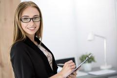 Jonge vrolijke bedrijfsvrouw die zich met het knippen van raad bevinden Stock Foto
