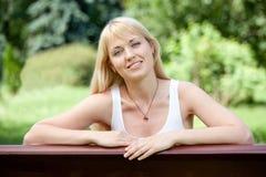 Jonge vrolijke blonde vrouw op de bank in de zomer Stock Afbeelding