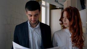 Jonge vrolijke collega's die over project spreken, die langs gang van bedrijf lopen stock footage