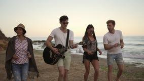 Jonge vrolijke gelukkige vrienden die op het zand door de oceaan, het spelen gitaar, het zingen liederen lopen en het dansen Slow stock video