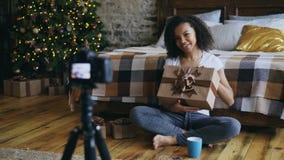 Jonge vrolijke gemengde de opname videoblog van het rasmeisje over de giftdoos van verpakkingskerstmis thuis Royalty-vrije Stock Afbeeldingen