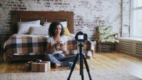 Jonge vrolijke gemengde de opname videoblog van het rasmeisje over de giftdoos van verpakkingskerstmis thuis Royalty-vrije Stock Afbeelding